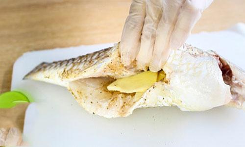 Cho gừng thái miếng cá bụng cá trước khi hấp